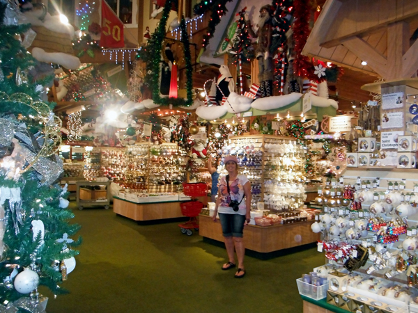 karen duquette and a small display of ornaments inside bronners christmas wonderland